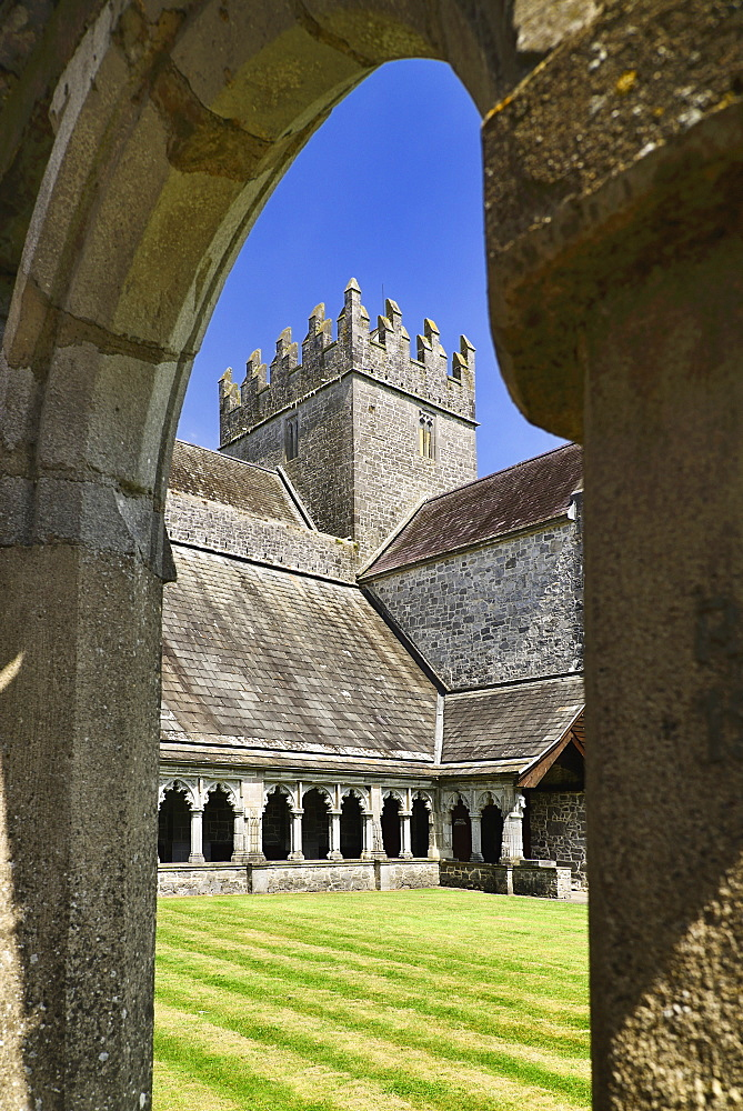 Ireland, County Tipperary, Holycross Abbey, view through an arch of the cloister.