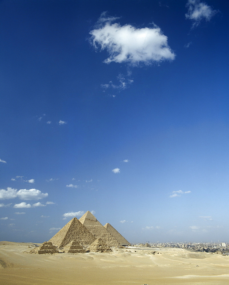 EGYPT Cairo Area Giza Pyramids in desert landscape with shadows cast over sand and Cairo beyond.