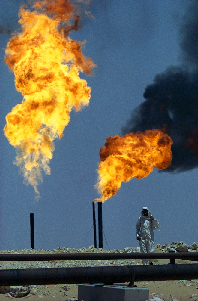 SAUDI ARABIA  Industry Flaming gas on oil field with man standing behind pipe in foreground.