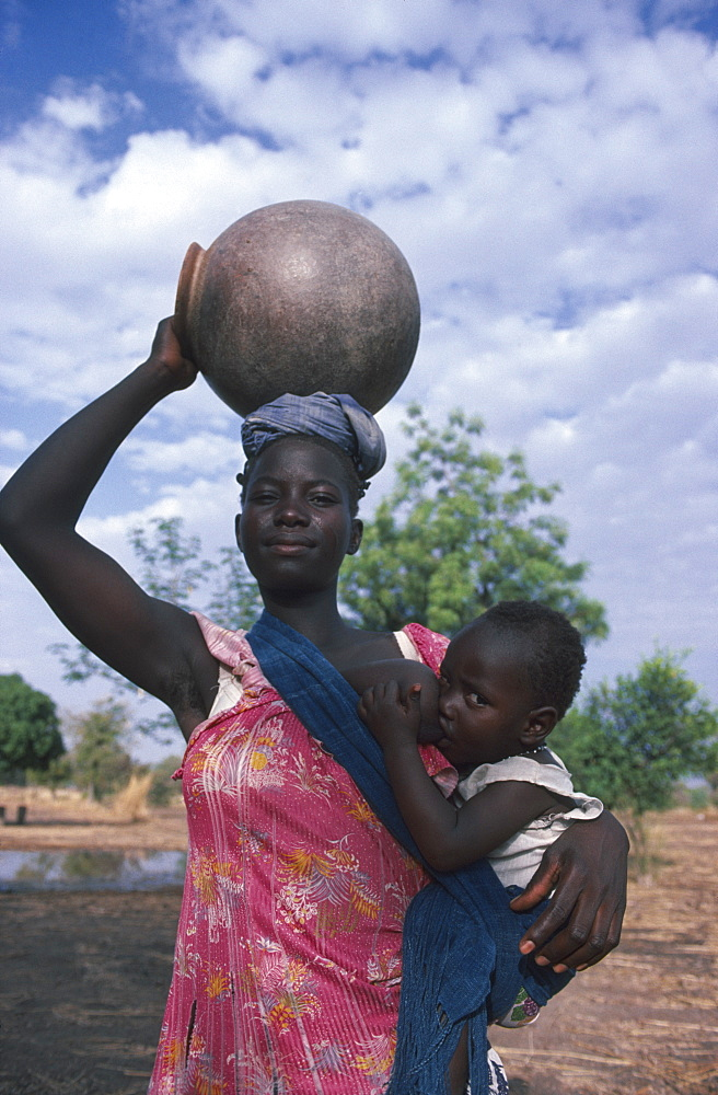 BURKINA FASO Children Woman breastfeeding child in sling at her side while carrying water pot on her head.
