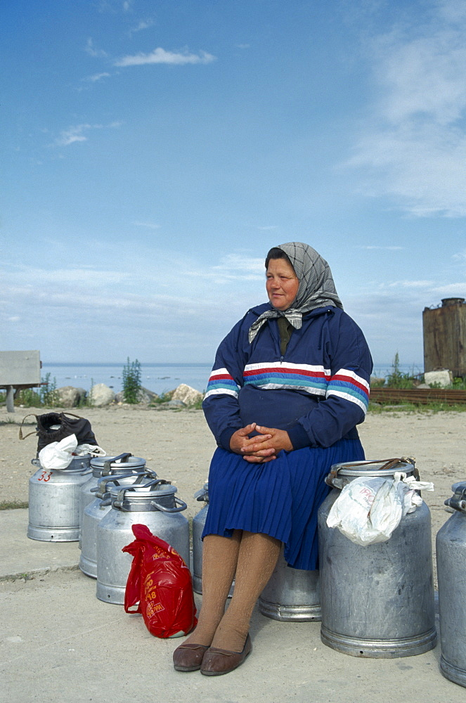 ESTONIA Work Woman sitting on milk cans waiting for ferry on the Baltic Coast.    - 797-2120