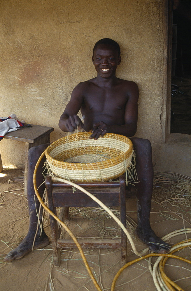 LIBERIA  Upper Lofa Young man making coil basket.