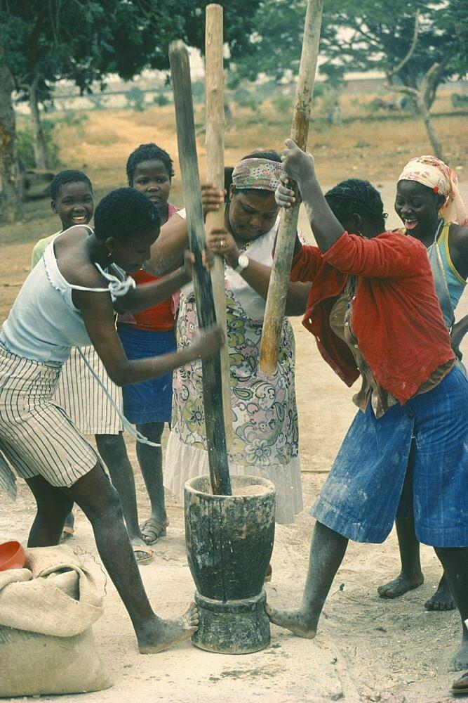 ANGOLA  Work Village women pounding grain.