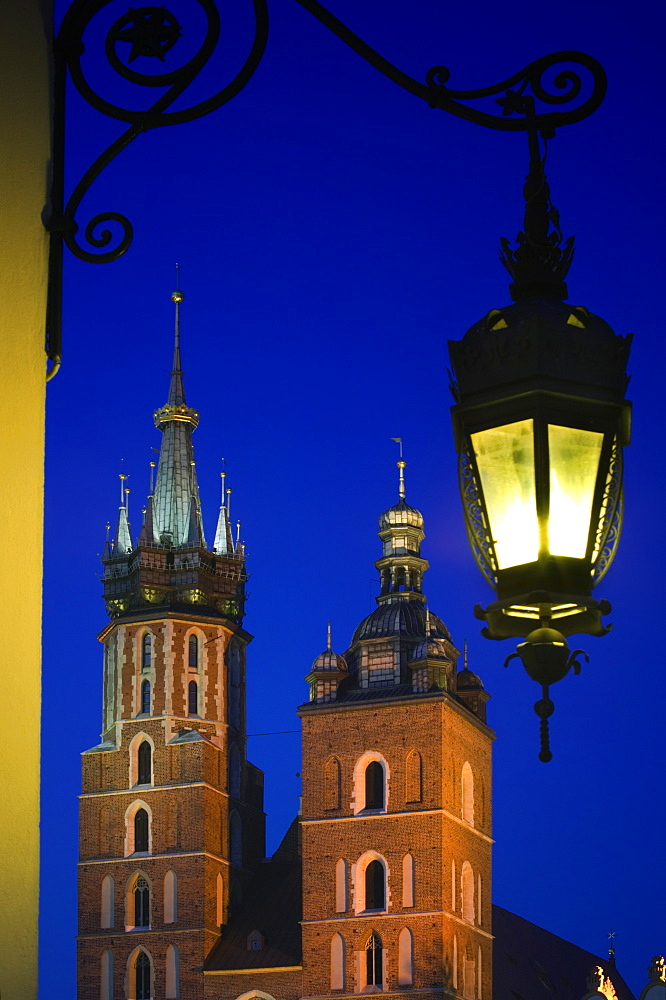 POLAND  Krakow Detail of St Marys Church in Rynek Glowny  Night time with lit lamp with decorative bracket on wall. Eastern Europe Holidays Travel Tourism