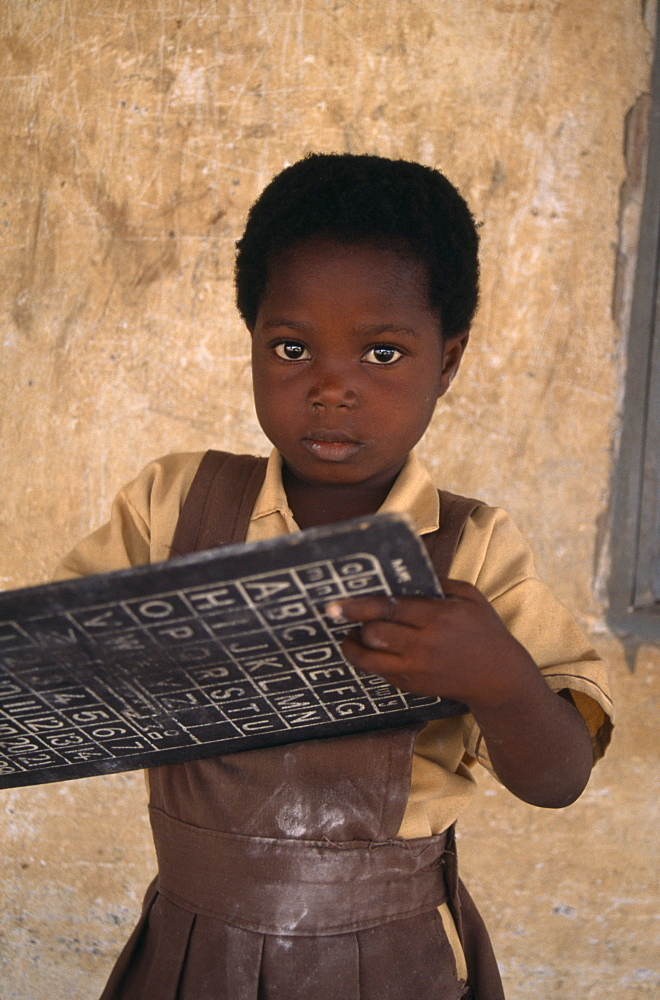 GHANA  Education Portrait of pupil from primary school in village near Accra holding small blackboard printed with alphabet and numbers.