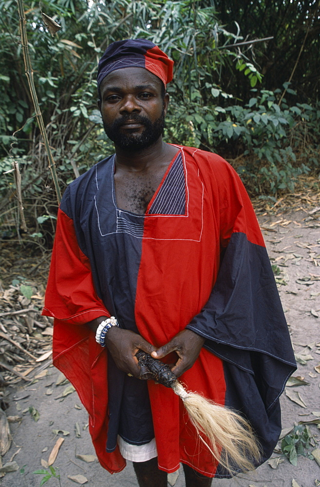 GHANA  Tribal People Portrait of traditional priest and healer in village near Accra wearing black and red robes.