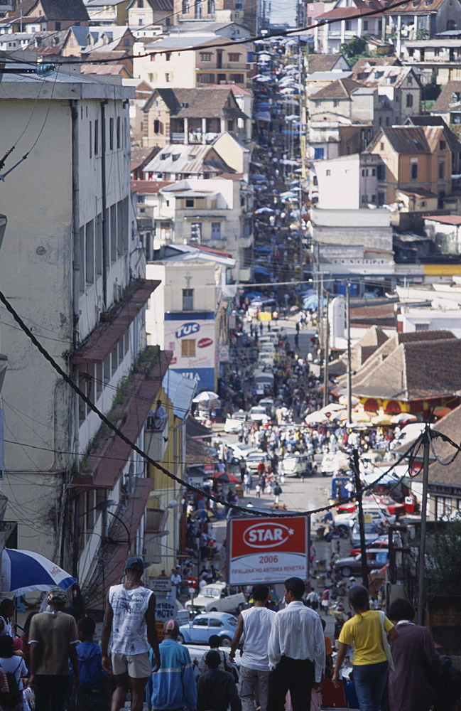 MADAGASCAR  Antananarivo Downtown area. People walking down towards a busy road running between buildings and shopfronts filled with people and cars