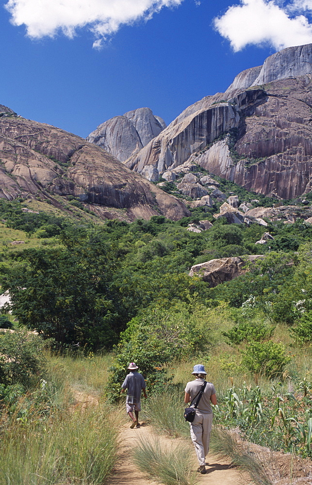 MADAGASCAR  Ambalavao A tourist being lead by a guide towards rocky mountains and trees in the Anjaha Nature Reserve   Anja