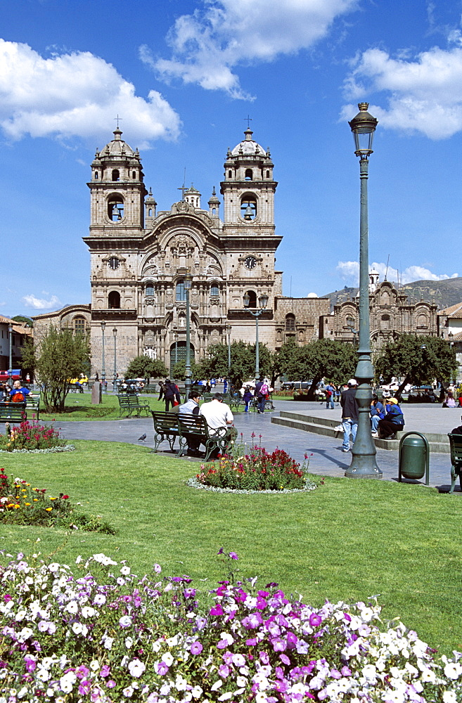 PERU  Cusco Looking across Plaza de Armas to Iglesia La Compania de Jesus. Cuzco Travel Tourism Holiday Vacation Explore Recreation Leisure Sightseeing Tourist Attraction Tour Destination Plaza De Armas Cusco Cuzco Peru Peruvian South Southern America Latin Sacred Valley Of The Inca Incas Vivid Vibrant City Town Square Tranquil Tranquility Tradition Traditional Culture Cultural Buildings Architecture Architectural Ethnic UNESCO World Heritage Site Andes Andean View Vista Spanish Colonial Scenic Picturesque Backdrop People Visitors Park Garden Path Pathway Iglesia La Compania Jesus Jesuit Church Churches Religion Religious Pray Prayer Worship Worshipping Worshiping Christianity Holy Divine Christian Theology Faith Sacred Devout Catholic Catholicism Spectacular Beautiful Quiet Blue Sky Magnificent Lawn Grass Flowers Calendar American South America