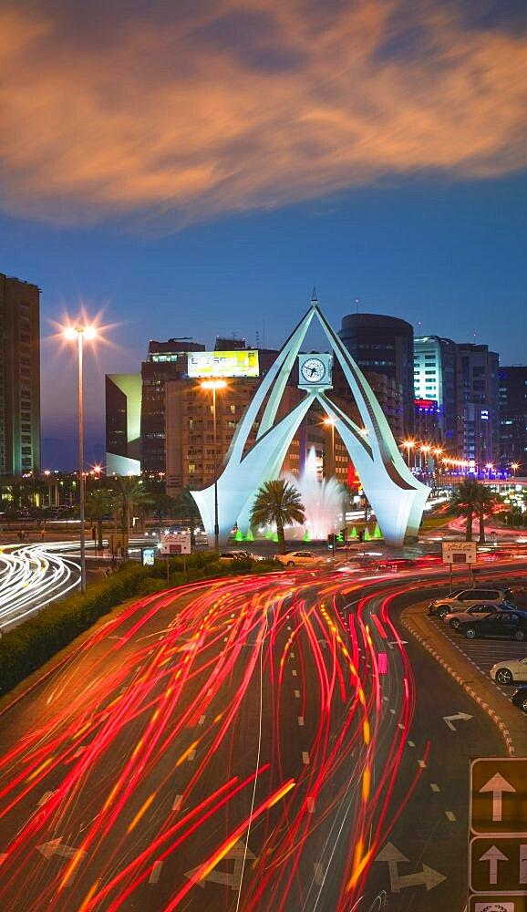 UAE  Dubai The Clock Tower roundabout in Rigga at dusk. Modern Architecture Middle East Dubai UAE Asia Holidays Tourism Travel United Arab Emirates Traffic Red Sunset Clock Time Transport Blur Al-Imarat Al-Arabiyyah Al-Muttahidah Arabic Asian Dubayy Emiriti