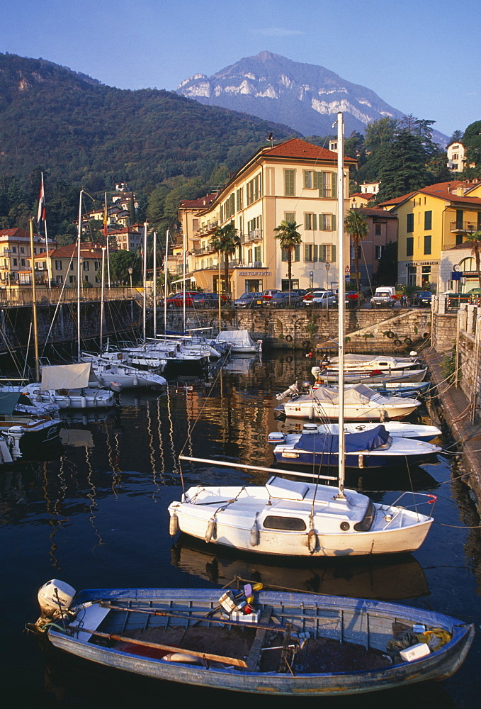 ITALY Lombardy Lake Como Menaggio.  Harbour with moored boats and waterside buildings with tree covered mountain backdrop.