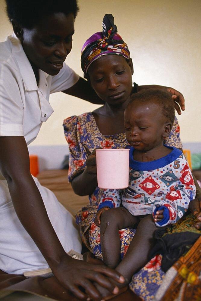Nurse comforting mother with child with malaria in hospital in Orukinga refugee camp near the Rwandan border, Medical, Uganda