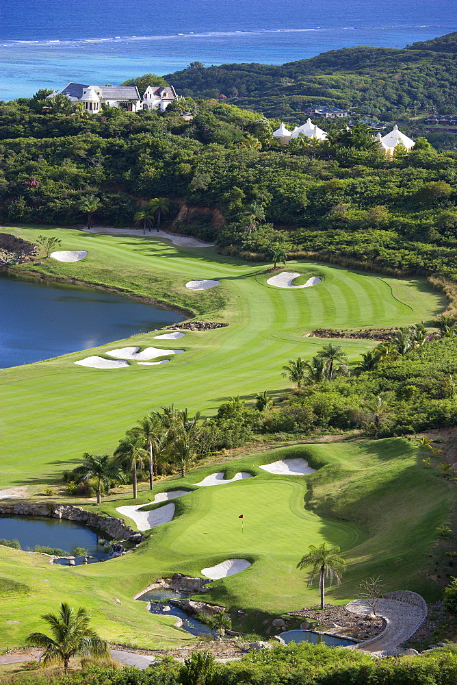Raffles Resort Trump International Golf Course designed by Jim Fazio, The 16th green which is the longest par 3 in the world the 17th fairway with the resort and coral reef beyond, Canouan, St Vincent & The Grenadines
