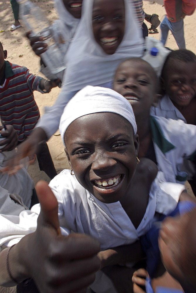 Tanji Village, Happy laughing children wanting to be photographed and trying to get the best position while having a break from lessons at the Ousman Bun Afan Islamic school, Child in centre foreground making a thumbs up gesture, Tanji, Western Gambia, The Gambia