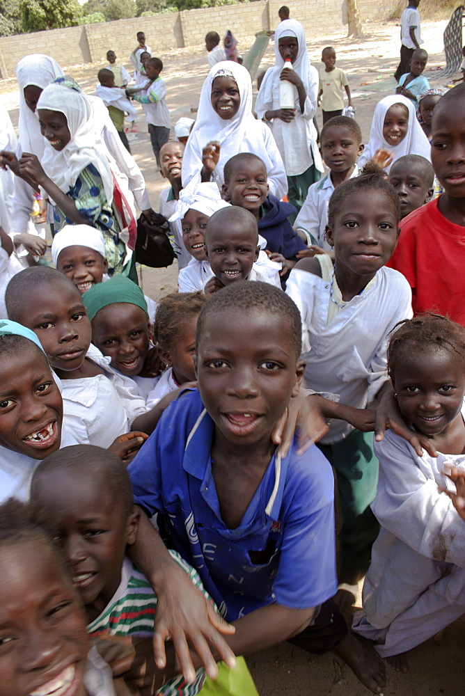 Tanji Village, Happy laughing children full of energy and wanting to be photographed trying to get the best position while on a break from lessons at the Ousman Bun Afan Islamic school, Tanji, Western Gambia, The Gambia