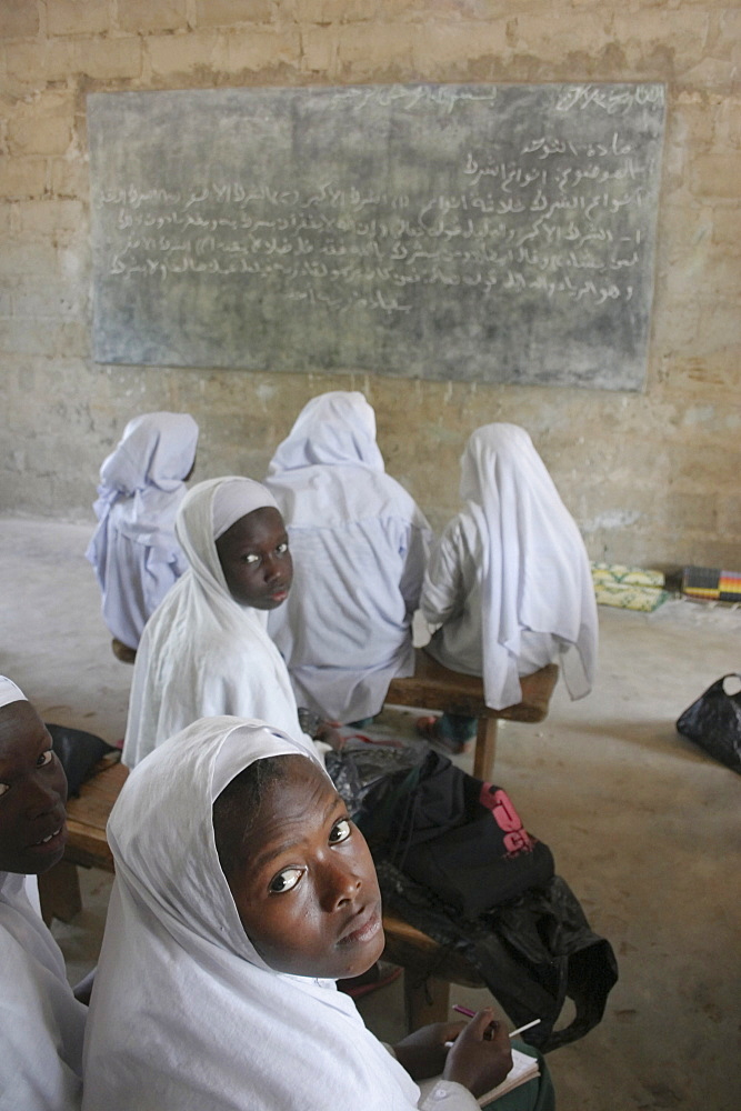 Tanji Village, African Muslim girls wearing white headscarves attending a class at the Ousman Bun Afan Islamic school, Girls in foreground looking back towards the camera, Tanji, Western Gambia, The Gambia