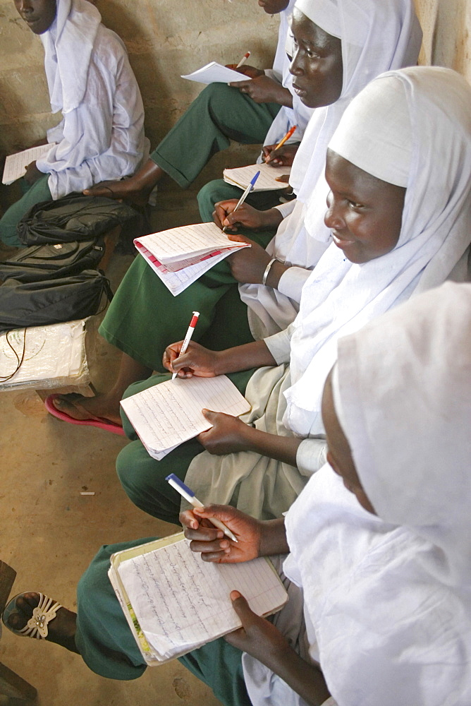 Tanji Village, African Muslim girls wearing white headscarves while attending a class at the Ousman Bun Afan Islamic school sitting in line writing in exercise books, Tanji, Western Gambia, The Gambia