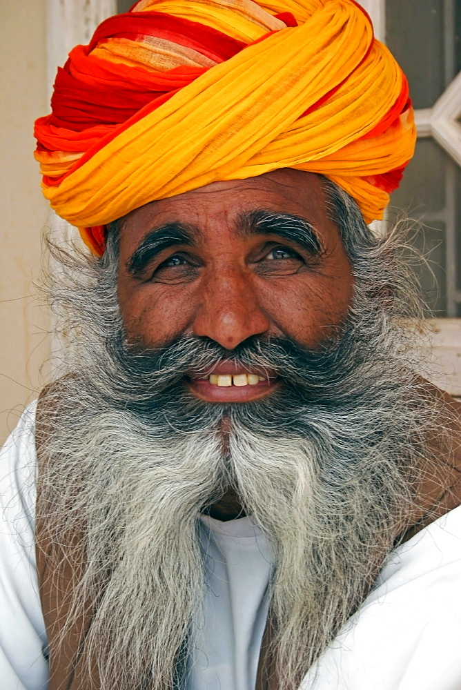 Meherangarh Fort, Head and shoulders portrait of a smiling Indian man with long grey beard wearing red yellow and orange turban, Jodhpur, Rajasthan, India