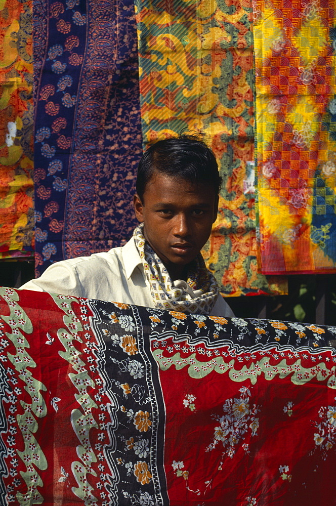 Fabric trader holding up printed cotton, Asia