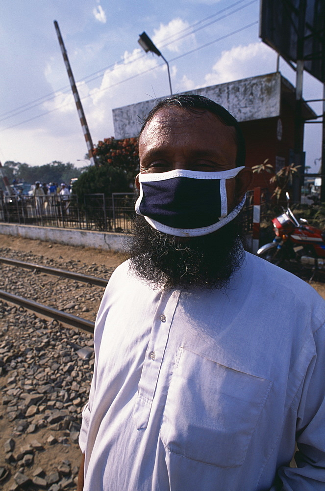Bearded man wearing a mask covering his mouth and nose against air pollution, Bangladesh, Asia