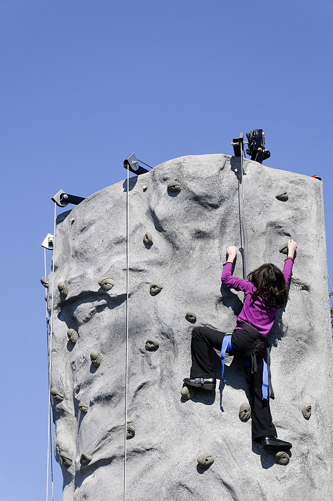 Young girl climbing manmade rockface using safety harness, America