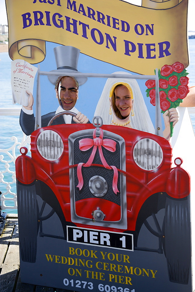 England, East Sussex, Brighton, Man and woman with their faces in amusement cut-out of wedding car that says Just Married On Brighton Pier which also serves as a bookings advertisement for marriage ceremonies on the Pier itself.