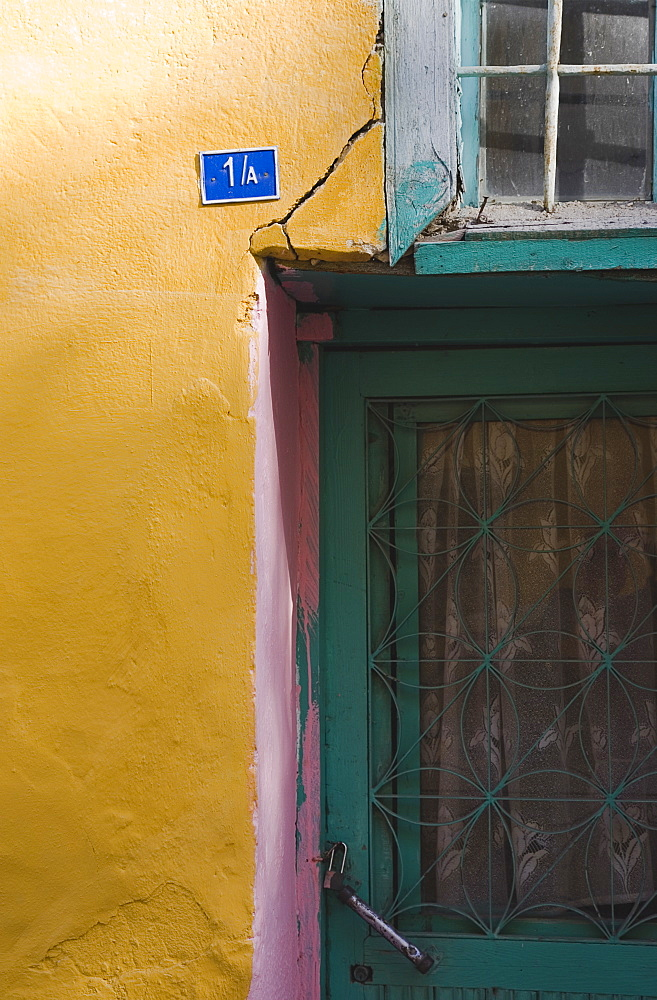 Turkey, Aydin Province, Kusadasi, Detail of exterior facade of house in the old town numbered 1A With yellow and pink painted walls and turquoise painted door and window frames