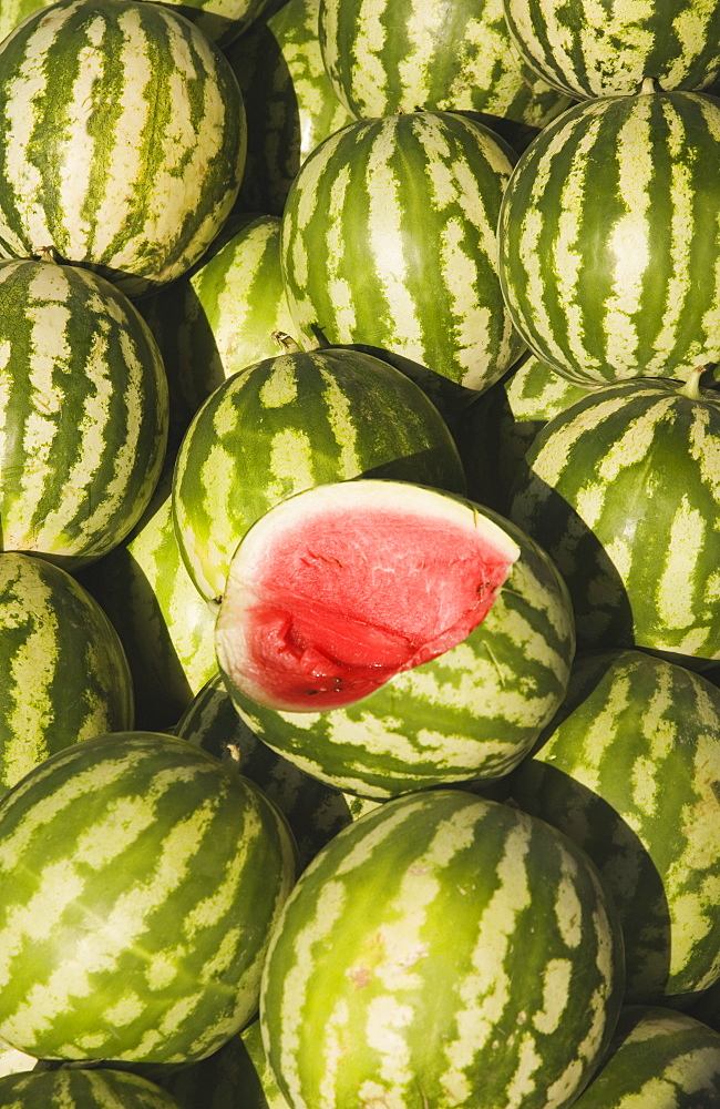 Turkey, Aydin Province, Kusadasi, Fresh watermelon on sale at town produce market with fruit at centre cut open to reveal red flesh and seeds
