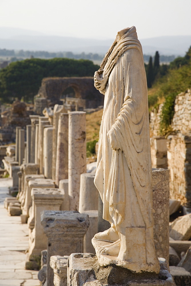 Turkey, Izmir Province, Selcuk, Ephesus, Headless statue on plinth in line of ruined pillars and empty pedestals in antique city of Ephesus on the Aegean sea coast