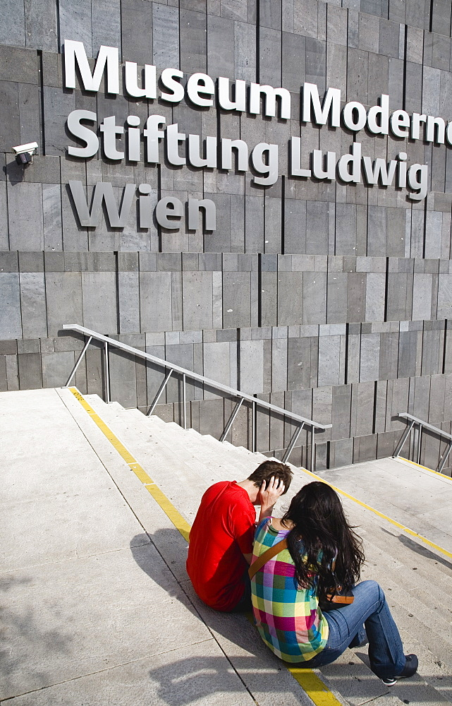 Austria, Vienna, Neubau District, Young student couple sitting on the steps of the Museum of Modern Art, Museum Moderner Kunst Stiftung Ludwig Wien or MUMOK