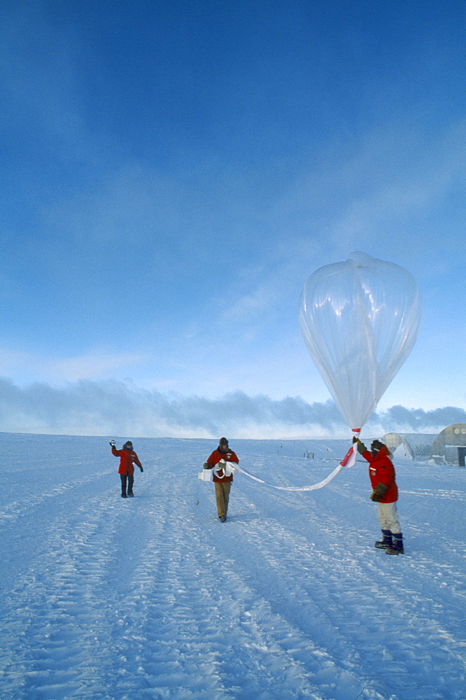 ANTARCTICA  South Pole Three figures launching a balloon to measure amounts of ozone in the air at various altitudes.   US Amundsen-Scott South Pole Station.