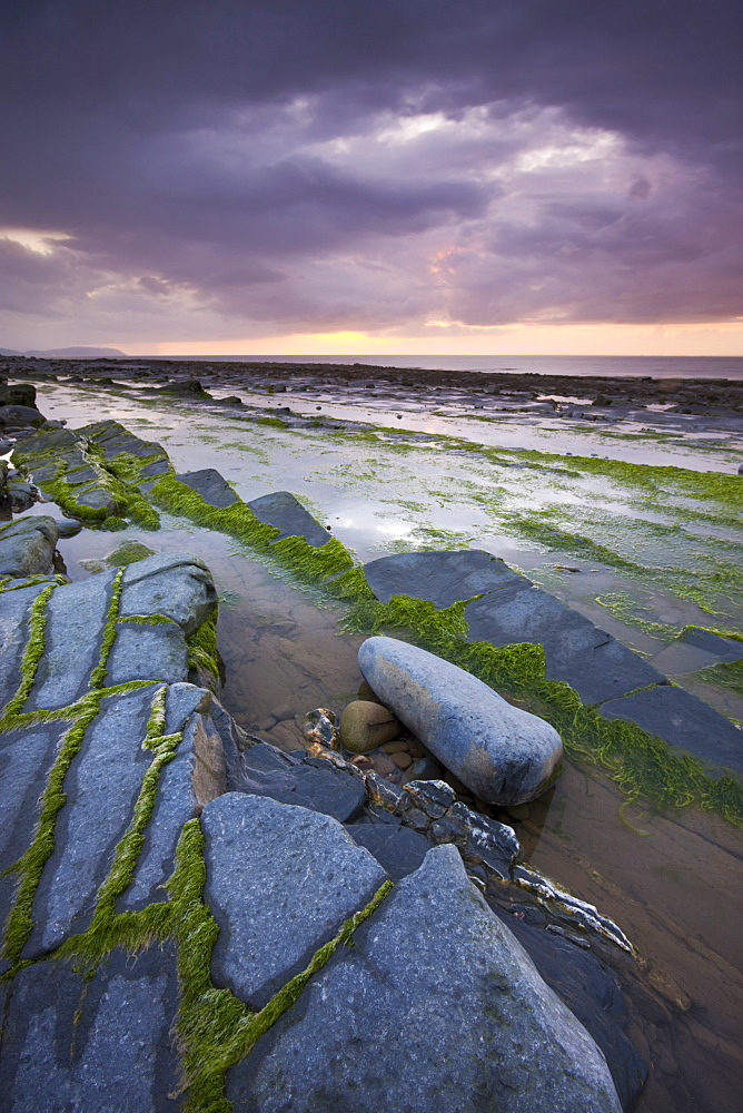 Stormy sunset over the Bristol Channel, viewed from the rocky shores of Kilve Beach, Somerset, England, United Kingdom, Europe