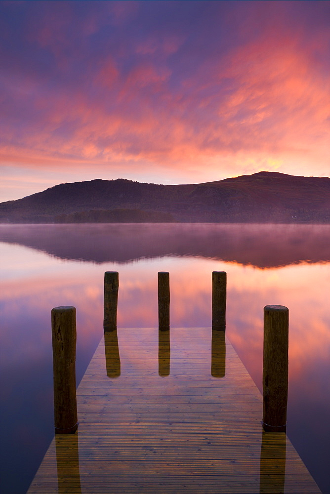 Fiery autumn sunrise over Derwent Water from Hawes End jetty, Lake District National Park, Cumbria, England, United Kingdom, Europe