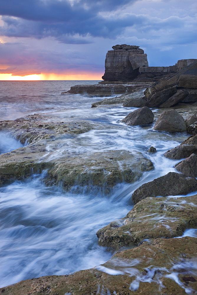Waves crash against the rocky coast of Portland Bill at sunset. Isle of Portland, Jurassic Coast, UNESCO World Heritage Site, Dorset, England, United Kingdom, Europe