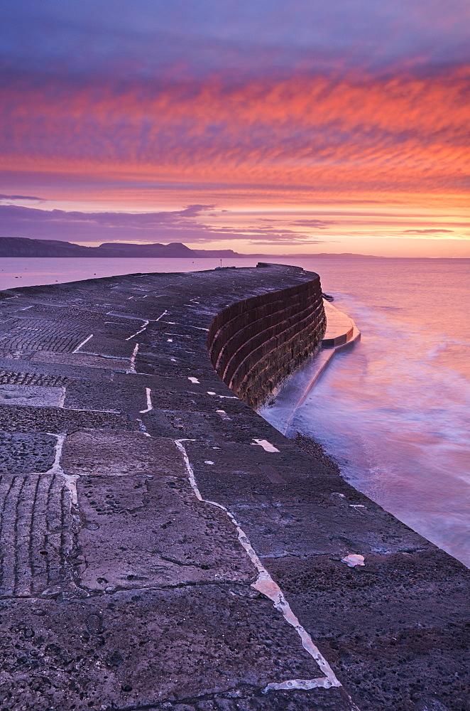 Spectacular winter sunrise above The Cobb harbour wall, Lyme Regis, Dorset, England, United Kingdom, Europe