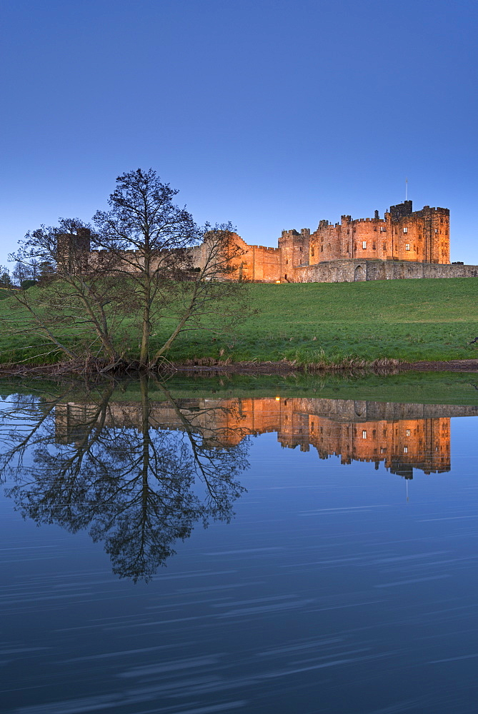 Alnwick Castle reflected in the River Aln at twilight, Northumberland, England, United Kingdom, Europe