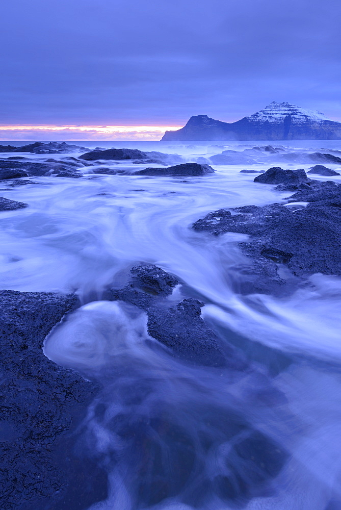 Surging waves rush over the basalt ledges of Gjogv at dawn, Eysturoy, Faroe Islands, Denmark, Europe