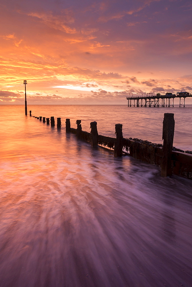 Beautiful colourful sunrise above the wooden groynes and pier at Teignmouth in Devon, England, United Kingdom, Europe - 799-3540