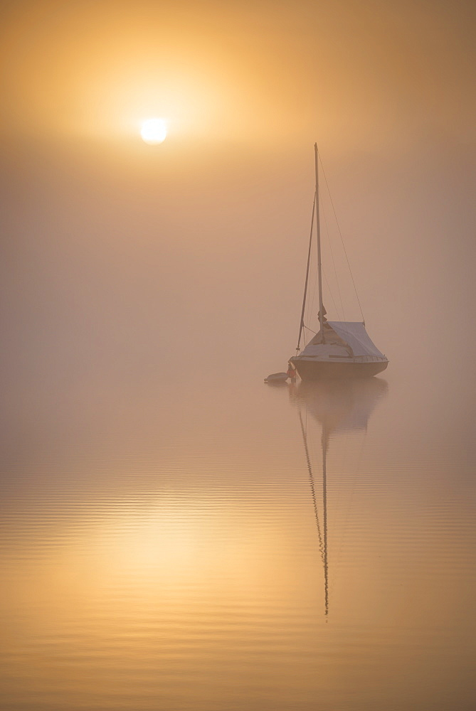 Sun rising over a sailing boat moored on a misty Wimbleball Lake, Exmoor National Park, Somerset, Engtland. Spring (May) 2017.