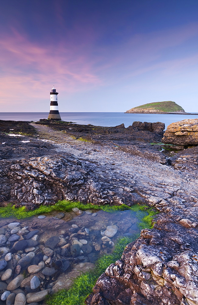 Twilight on the rocky Anglesey coast looking towards Penmon Point Lighthouse and Puffin Island, Anglesey, North Wales, Wales, United Kingdom, Europe