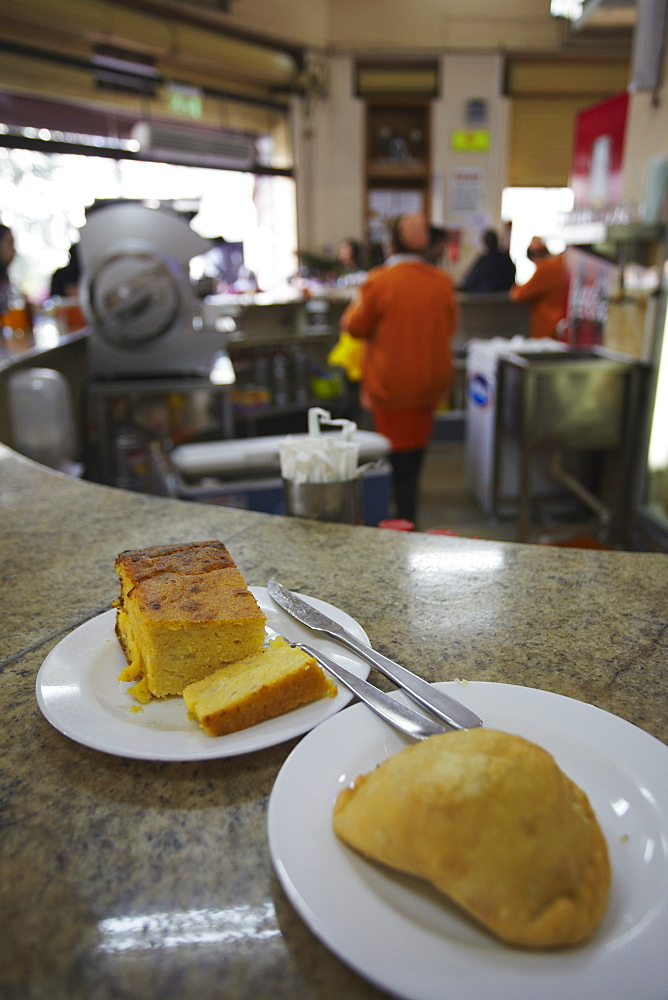 Sopa paraguaya (cornbread with cheese and onion) and empanada in Lido Bar, Asuncion, Paraguay, South America