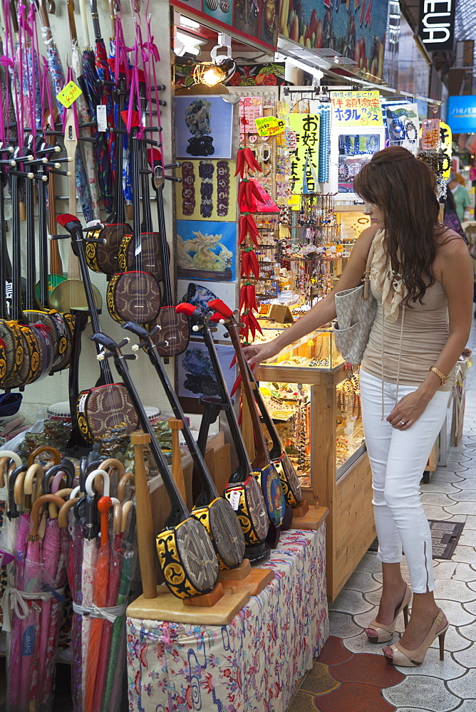 Woman looking at sanshin, an Okinawan musical instrument, in Ichibahon-dori indoor shopping arcade, Naha, Okinawa, Japan, Asia