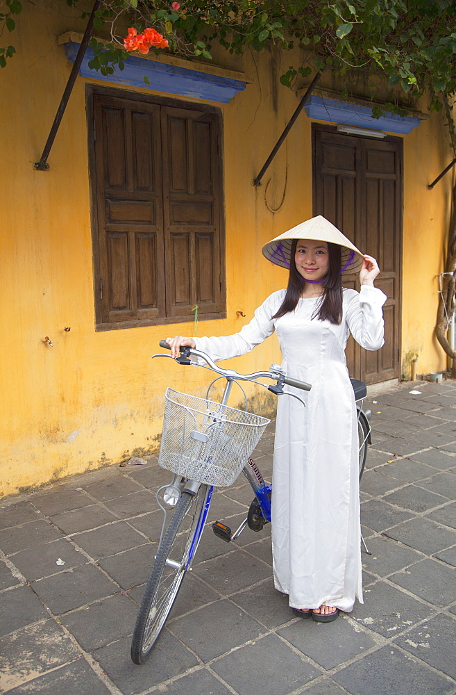 Woman wearing Ao Dai dress with bicycle, Hoi An, Quang Nam, Vietnam, Indochina, Southeast Asia, Asia