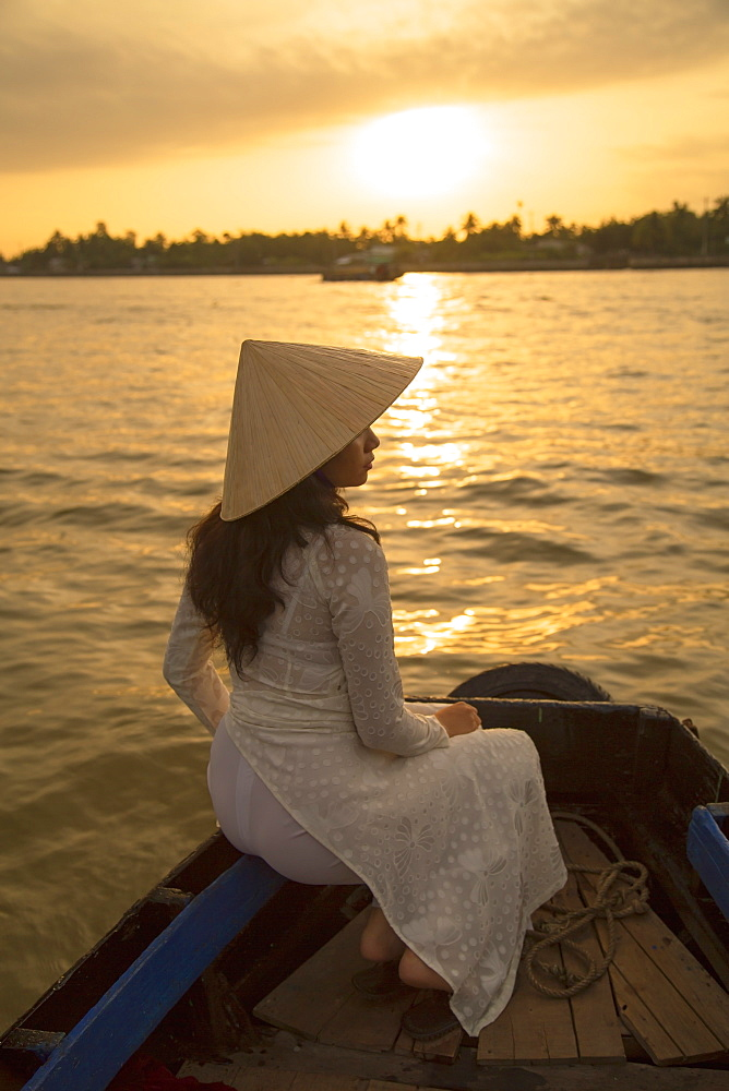 Woman wearing ao dai dress in boat at dawn, Can Tho, Mekong Delta, Vietnam, Indochina, Southeast Asia, Asia