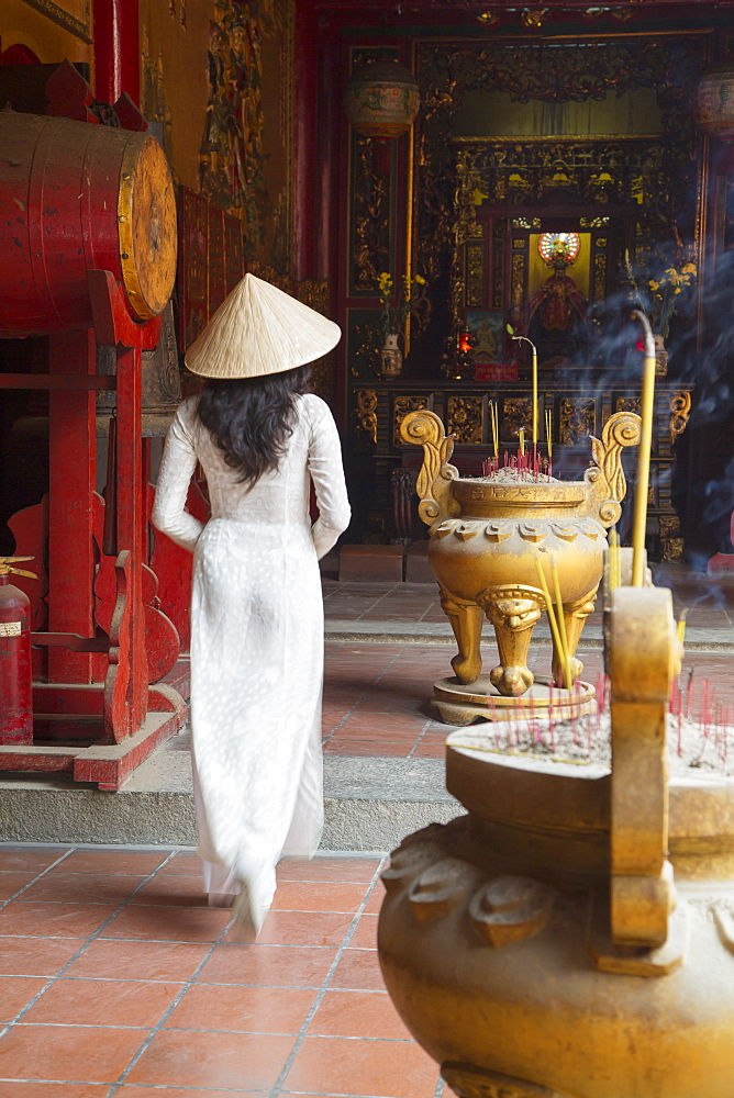 Woman wearing ao dai dress at Ha Chuong Hoi Quan Pagoda, Cholon, Ho Chi Minh City, Vietnam, Indochina, Southeast Asia, Asia