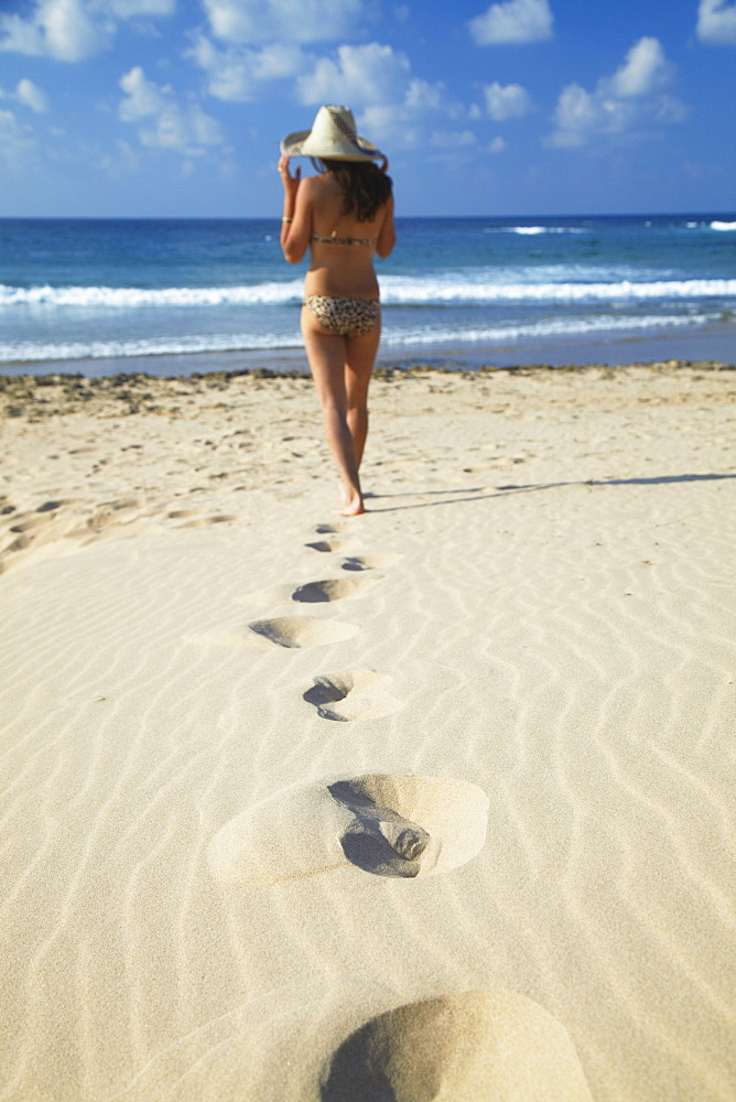 Woman walking on sand dunes, Tofo, Inhambane, Mozambique, Africa