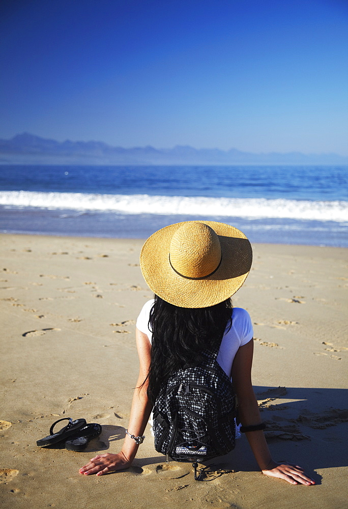 Woman relaxing on beach, Plettenberg Bay, Western Cape, South Africa, Africa