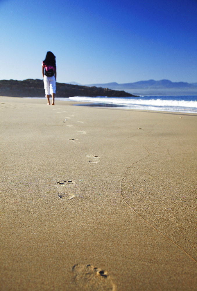 Woman walking on beach, Plettenberg Bay, Western Cape, South Africa, Africa