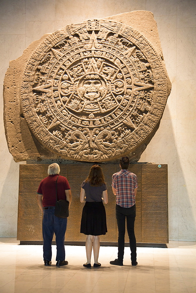 Tourists looking at Aztec calendar stone, National Museum of Anthropology, Mexico City, Mexico, North America