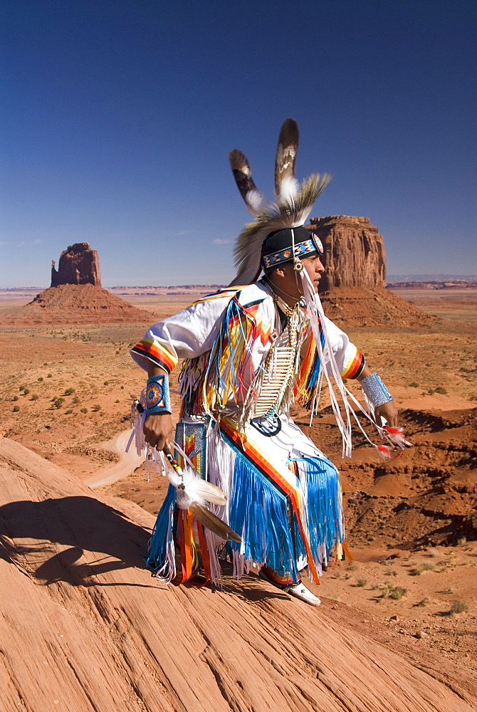 Navajo man dressed in traditional costume dancing, with Merrick Butte on the right and East Mitten Butte on the left in the background, Monument Valley Navajo Tribal Park,  Utah, United States of America, North America - 801-270
